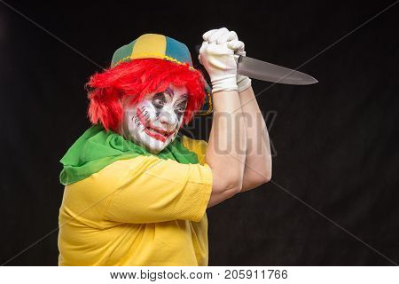 Scary clown with a horrible make-up laughs and with big knives in hands on a black background