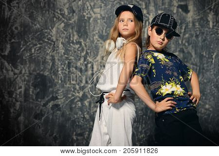 Two cool modern kids posing together in hip-hop style clothes. Children's fashion.
