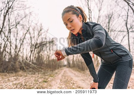 Sport watch run woman checking smartwatch tracker. Trail running runner girl looking at heart rate monitor smart watch in forest wearing jacket sportswear. Female athlete jogger training in woods.