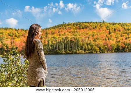 Autumn girl at forest lake enjoying watching nature view. Autumn forest colors woman relaxing at countryside vacation getaway. Outdoor autumn landscape tranquility.