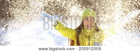 Happy winter fun woman throwing snow banner. Panorama crop of outdoor lifestyle girl playing in snow outside laughing in yellow coat, hat, gloves and scarf.