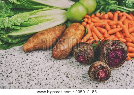 Autumn vegetables beets and sweet potatoes harvest background. Farm vegetable such as green apples, carrots, romaine lettuce for a fall salad recipe.