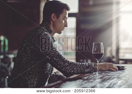 Handsome young man spends time in a wine restaurant.