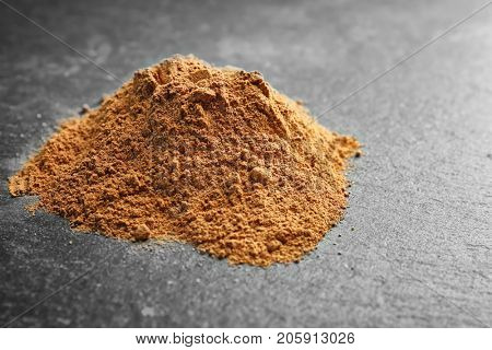 Pile of cumin spice on grey background