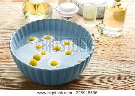 Chamomile flowers floating in bowl of water on wooden table