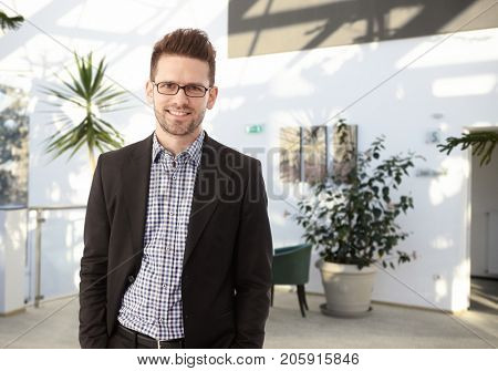 Portrait of a young and smart businessman - a successful financial advisor smiling in office lobby.