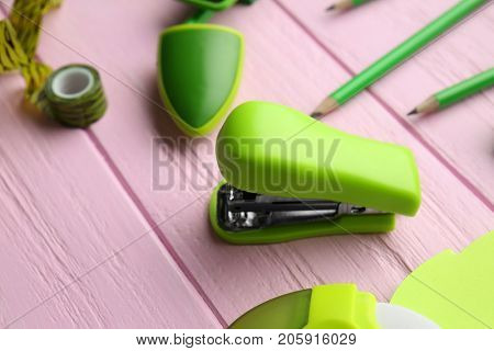 Bright green stapler on pink wooden table