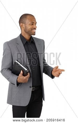 Smiling Afro-American businessman with personal organizer pointing, cutout on white.