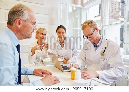 Doctor writing prescription to senior patient for medicament