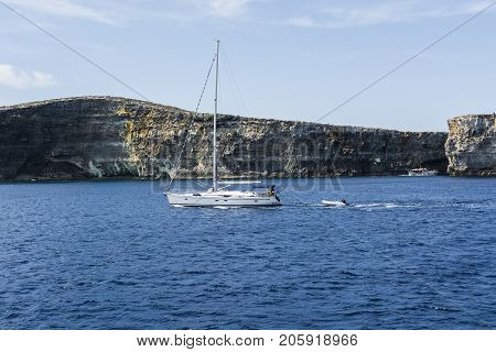 Comino is a small island of the Maltese archipelago between the islands of Malta and Gozo in the Mediterranean Sea. Yacht at the rugged coastline delineated by sheer limestone cliffs and dotted with deep caves