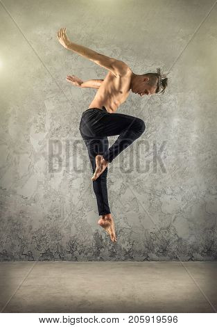 Man dancer, in beautiful dynamic jump action figure on the grunge background.