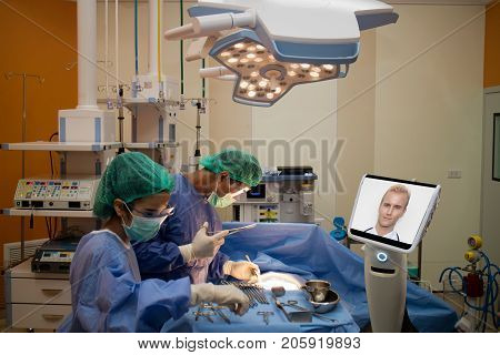 doctor surgery patient in operating room in hospital and talk consult with specialist doctor by telepresence robot during emergency. robot(artificial intelligence) technology for betterefficiency