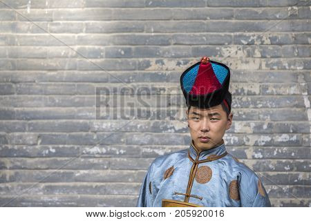 mongolian man in traditional outfit near old Temple in Ulaanbaatar