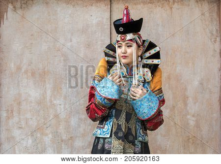 Mongolian woman in traditional outfit near old Temple in Ulaanbaatar