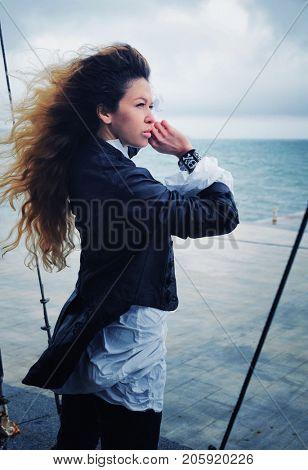 Calm fashion woman posing outdoor near ocean in windy day