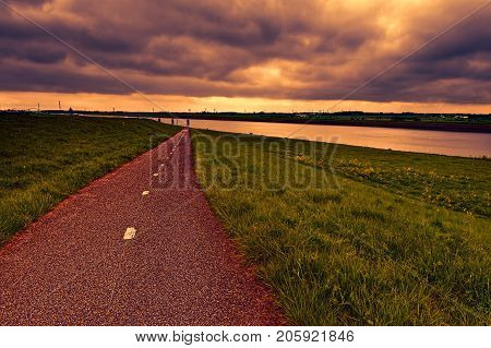 Agriculture on land reclaimed from the see in Netherlands at sunset. Asphalt road along protective dam and canal in Holland