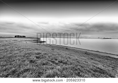 Dunes and sea at the North Sea shore in Holland. Dutch landscape with dike protects against flooding. Black and white picture
