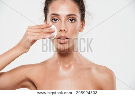 Cropped beauty portrait of an attractive brunette woman with soft healthy skin removing make up with cotton pad isolated over white background