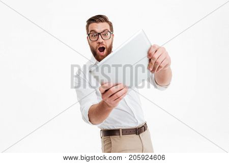 Picture of handsome young bearded man standing near copyspace over white wall background isolated. Looking aside play games by tablet computer.