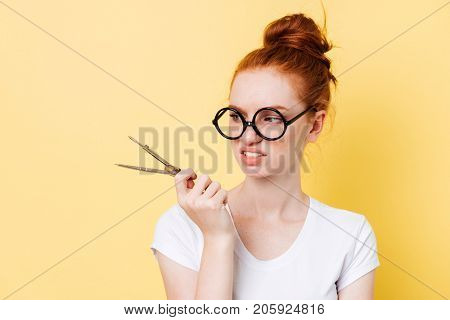 Displeased ginger woman in eyeglasses looking on dividers over yellow background