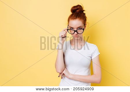 Calm ginger woman in eyeglasses looking through eyeglasses at the camera over yellow background