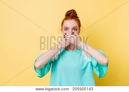 Suprised ginger woman covering her mouth and looking at the camera over yellow background