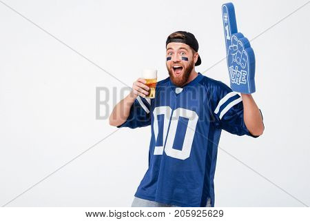 Picture of emotional man fan in blue t-shirt wearing fan finger number one glove standing isolated over white background. Looking camera drinking beer.