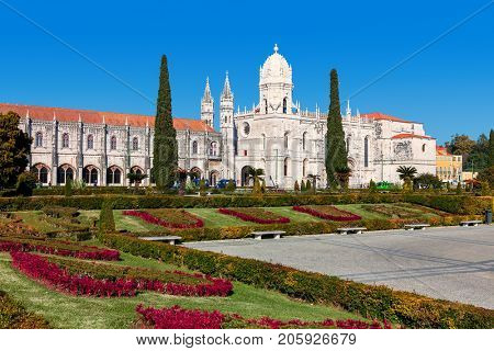 View of urban park with flowers and Jeronimos (aka Hieronymites) Monastery under blue sky in Lisbon, Portugal.