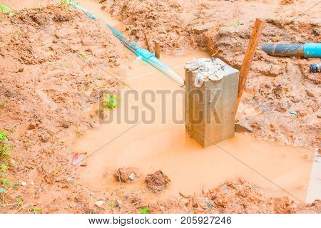 cement pillar in pit which has water And plumbing in construction work site