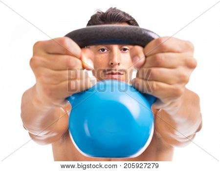 Handsome muscular man holding kettle bell, isolated on a white background