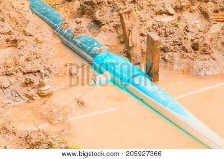 repair plumbing PVC broken pipe in hole which has water with copy space add text