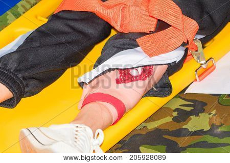 leg patient injured on stretcher yellow for emergency paramedic service Injury with medical equipment in training emergency rescue situation