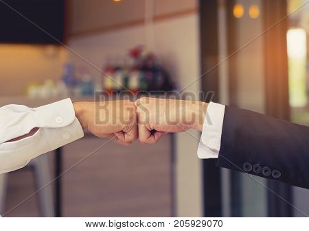 Closeup Giving fist bump hands of businessmen together teamwork partner and join group successul project