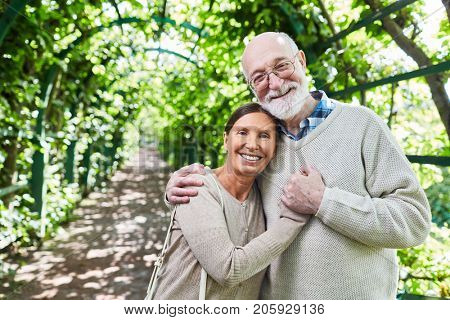 Aged couple standing in embrace in green alleyway in natural environment