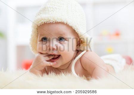 Cute little baby girl weared in white hat sucking her fingers