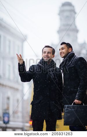 Handsome bearded entrepreneur conducting excursion for his foreign business partner after productive negotiations, snow falling, blurred background