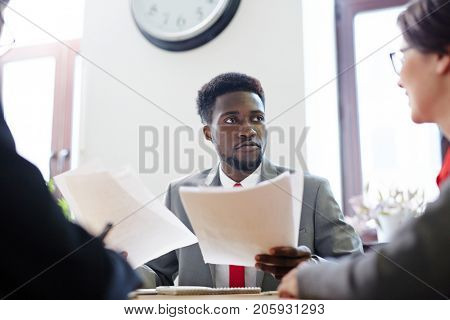 Businessman with papers listening to one of colleagues during discussion