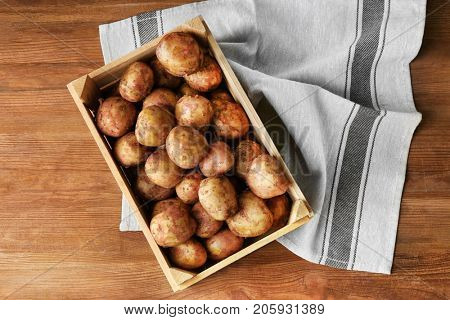 Wooden crate with young potatoes on table