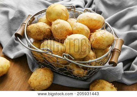 Metal basket with young potatoes on wooden table