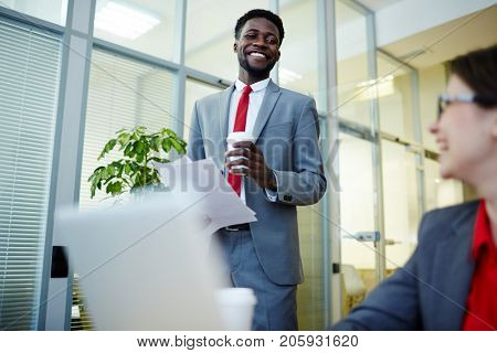 Happy young intercultural professionals interacting during work in office