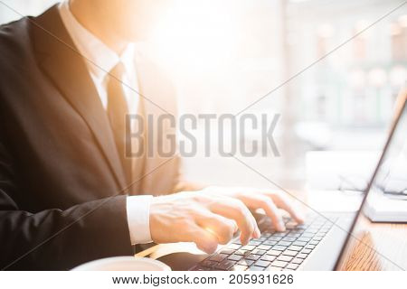Profile view of unrecognizable white collar worker in suit sitting at office desk and working on promising project with help of laptop
