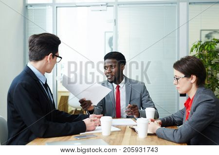 Confident employers interviewing one of candidates for new vacancy