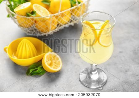 Composition with glass of lemon juice and fresh lemons on table