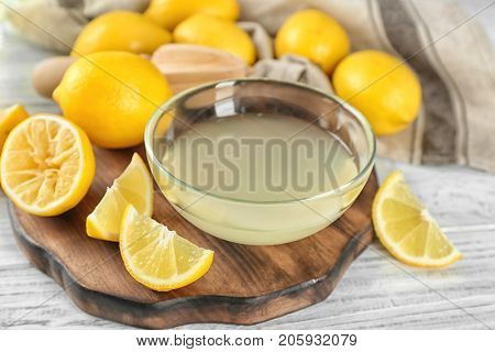 Composition with freshly squeezed lemon juice and lemons on table