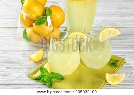 Two glasses of lemon juice and fresh lemons on table