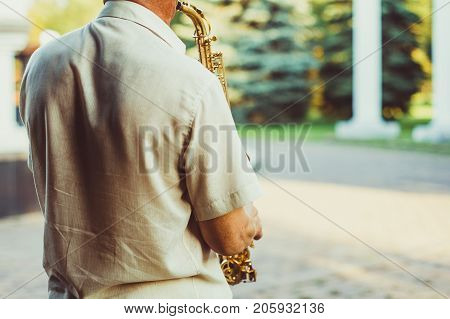 Novokuzneck Russia 16.07.2017: sax musician walking in the street during a celebration on blur background