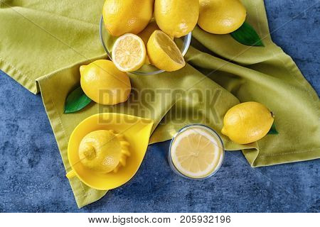 Glass of lemon juice, squeezer and fresh lemons on table