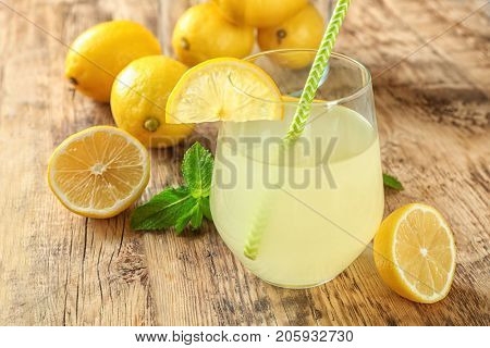 Composition with glass of lemon juice and fresh lemons on wooden table