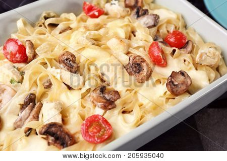 Delicious roasted turkey tetrazzini in baking dish on table, close up
