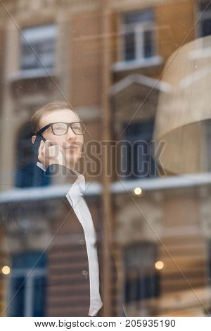 Confident ceo speaking to subordinate on smartphone by window